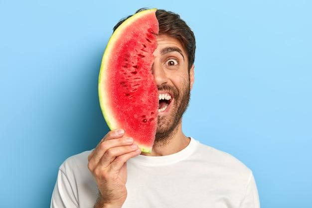 Geïsoleerde shot van lachende man op een zomerse dag met een plakje watermeloen Gratis Foto