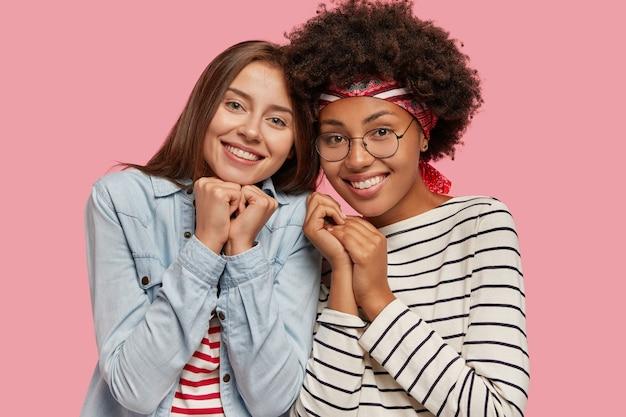 Geïsoleerde shot van twee tevreden multi-etnische jonge vrouwen staan dicht bij elkaar, hebben brede glimlach Gratis Foto