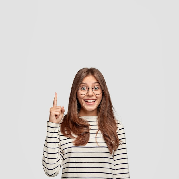 Geïsoleerde shot van vrolijke blanke vrouw met steil haar, toont vrije ruimte, wijst met wijsvinger voor uw reclame-inhoud, draagt casual gestreepte trui, geïsoleerd over witte muur Gratis Foto