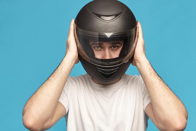 Geïsoleerde studio shot van zelfbepaalde serieuze jonge blanke mannelijke fietser nemen stijlvolle zwarte motorhelm Gratis Foto
