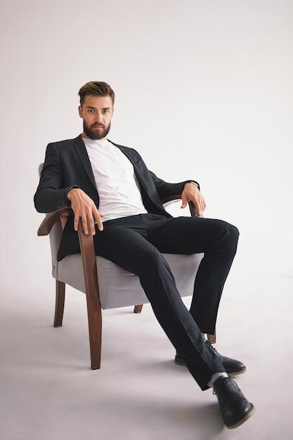 Geïsoleerde verticaal portret van succesvolle knappe stijlvolle jonge europese mannelijke baas met fuzzy bijgesneden baard dragen trendy herenkleding ontspannen in fauteuil en staren met serieuze blik Gratis Foto