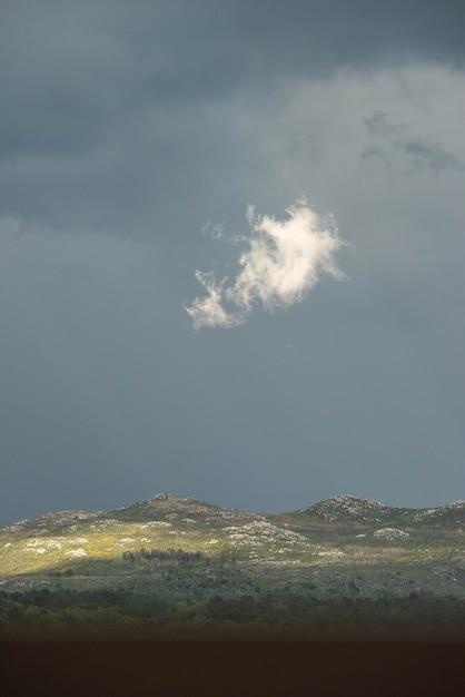 Geïsoleerde wolk verlicht door de zon in het midden van de storm Premium Foto