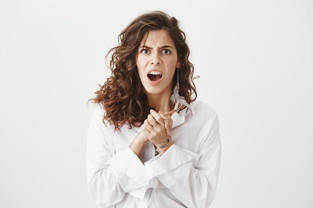 Gekke en gefrustreerde vrouw die fronst en teleurgesteld kijkt Gratis Foto