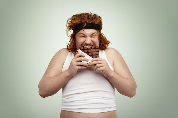 Gekke en hongerige jonge roodharige europese man met overgewicht en goede eetlust Gratis Foto