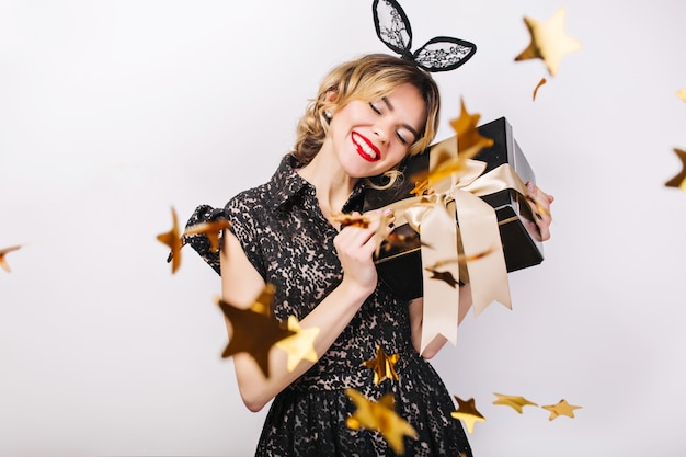 Gekke feesttijd van mooie vrouwen in elegante zwarte jurk met geschenkdoos, verjaardag, sprankelende gouden confetti, plezier, dansen. emotie gezicht, rode lippen, ogen dicht. Gratis Foto
