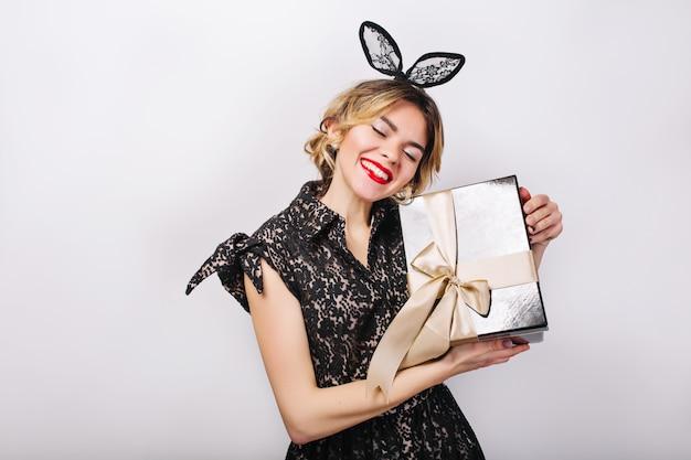 Gekke feesttijd van mooie vrouwen in elegante zwarte jurk met geschenkdoos verjaardag vieren, plezier maken, dansen. emotie gezicht, rode lippen, ogen dicht. Gratis Foto