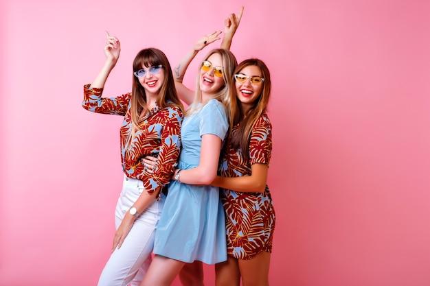 Gekke grappige foto van drie gelukkige beste vriendenmeisjes die samen genieten van een feestje, dansen en lachen, kleuraanpassing trendy elegante outfits en glazen, positieve stemming, roze muur Gratis Foto