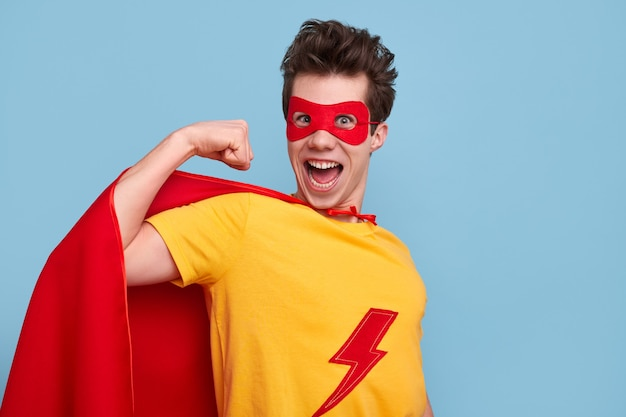 Gekke jonge man in superheld kostuum camera kijken met geopende mond en biceps tonen tegen blauwe achtergrond Premium Foto