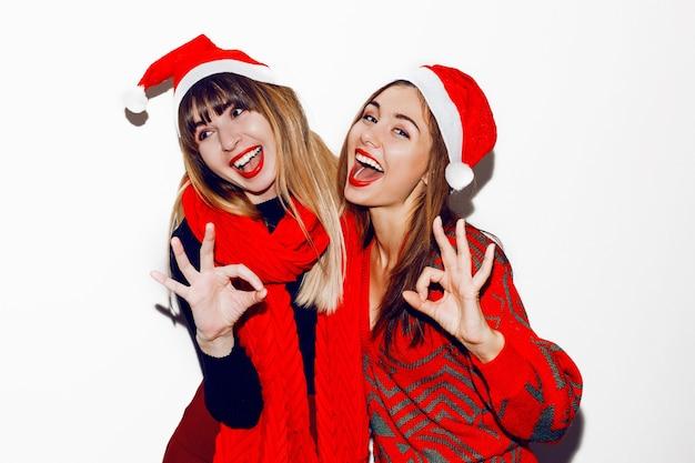 Gekke sfeer voor een nieuwjaarsfeest. twee dronken lachende vrouwen met plezier en poseren in schattige maskeradehoeden. rode trui en sjaal. ok laten zien door handen. Gratis Foto