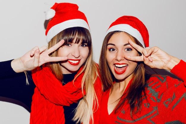 Gekke sfeer voor een nieuwjaarsfeest. twee dronken lachende vrouwen met plezier en poseren in schattige maskeradehoeden. rode trui en sjaal. tekenen tonen. witte tanden, lichte make-up. Gratis Foto
