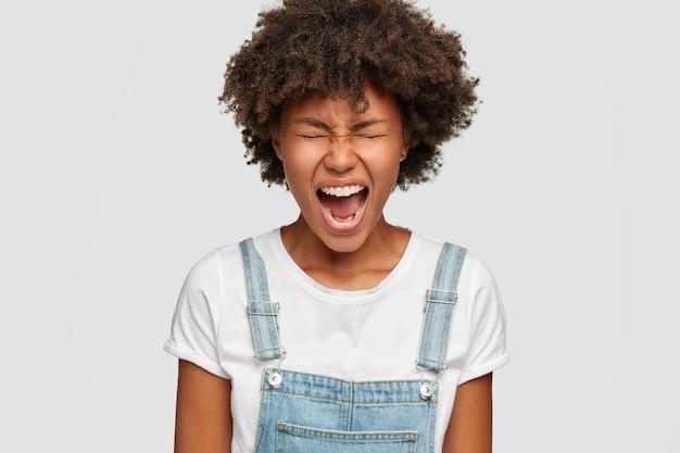 Gekke zwarte vrouw geïrriteerd door domme collega's, fronst gezicht van ongenoegen, huilt wanhopig Gratis Foto