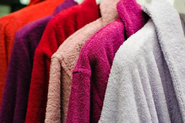 Gekleurde badstof badjassen opknoping op de winkel trempel Premium Foto