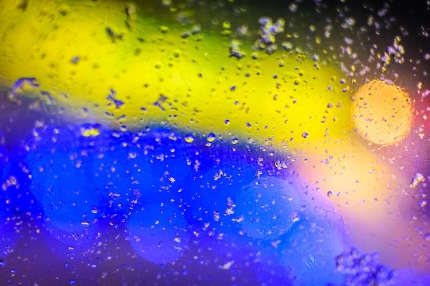 Gekleurde gele en blauwe textuur, wazige druppels water en lichte vlekken op het glas Premium Foto