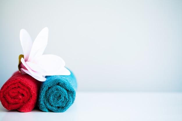 Gekleurde handdoeken en orchidee op witte lijst met exemplaarruimte op badkamerachtergrond. Premium Foto