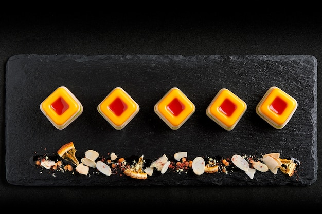 Gekleurde marmelade, neergelegd in een mooie lijn op een zwarte plaat. het concept van het fusievoedsel, rustig, exemplaarruimte. Premium Foto
