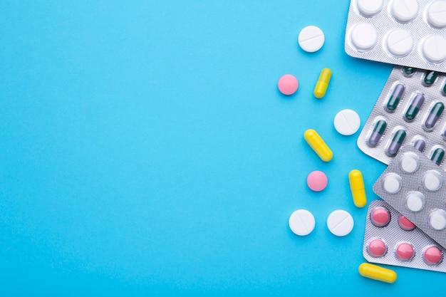 Gekleurde pillen en tabletten in blaar op blauw Premium Foto