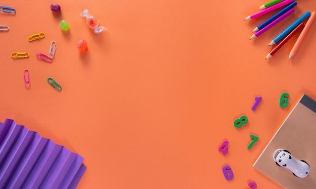Gekleurde verschillende schoollevering op oranje achtergrond. terug naar school achtergrond. plat lag, bovenaanzicht Premium Foto
