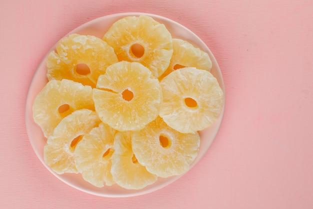 Gekonfijte ananas ringen in een plaat op een roze oppervlak Gratis Foto