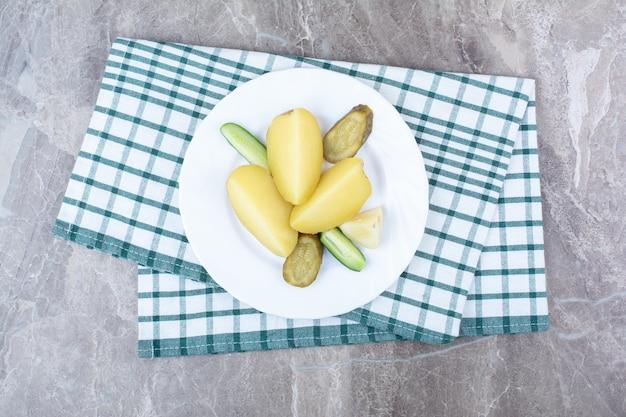Gekookte aardappelen en diverse augurken op een witte plaat. Gratis Foto