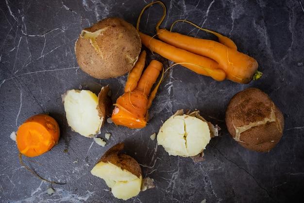 Gekookte aardappelen en wortelen liggen op een donkergrijze achtergrond. Premium Foto