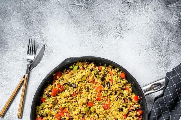 Gekookte bulgur met groenten in een pan. grijze achtergrond Premium Foto