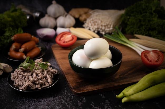Gekookte eieren in een zwarte kom, knoflook, worst, tomaten op een houten snijplank Gratis Foto