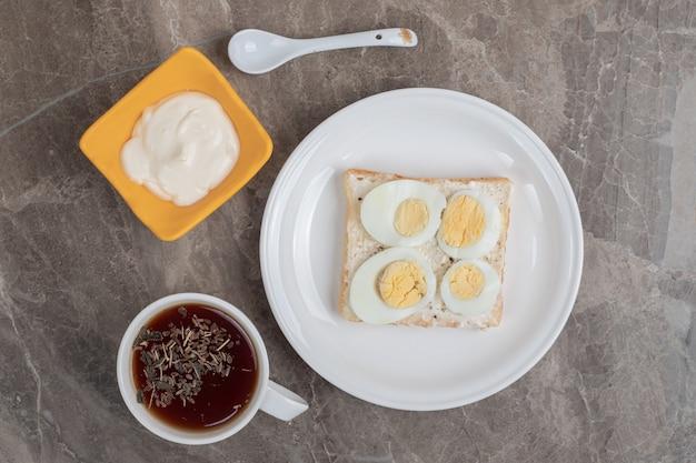 Gekookte eieren met brood op plaat en kopje thee. hoge kwaliteit foto Gratis Foto