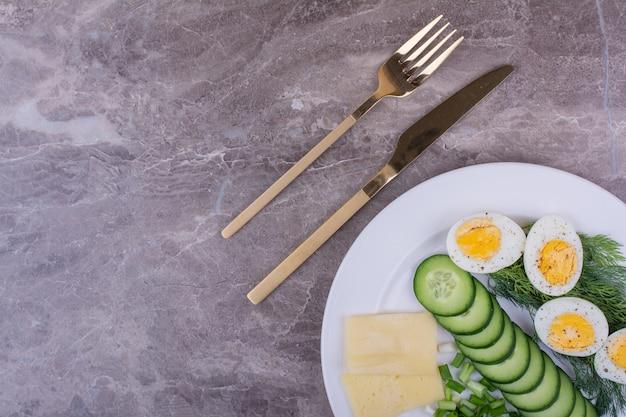 Gekookte eieren met een groene salade in een witte plaat. Gratis Foto
