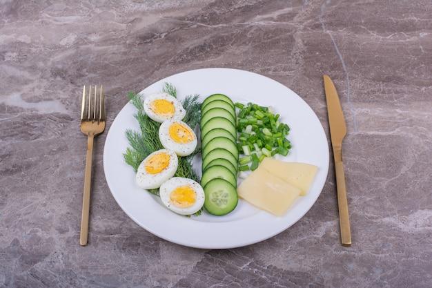 Gekookte eieren met gesneden komkommers en kruiden in een witte plaat. Gratis Foto