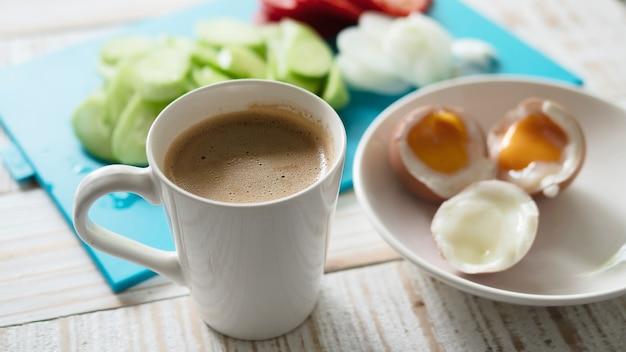 Gekookte eieren met verse komkommer salade en koffie kop ontbijt set - top uitzicht ontbijt eten concept Gratis Foto