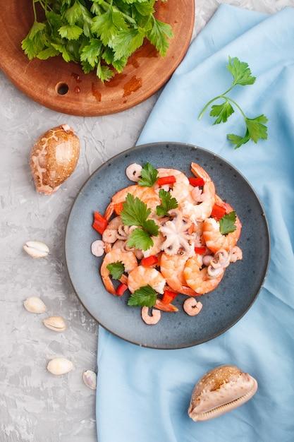 Gekookte garnalen of garnalen en kleine octopussen met kruiden op een blauwe keramische plaat op een grijze betonnen achtergrond Premium Foto
