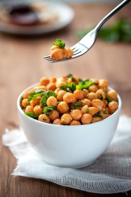 Gekookte kikkererwten met peterselie en paprika in een witte kom. vegetarisch eten. Premium Foto