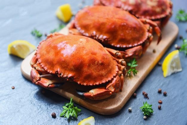 Gekookte krabben op houten bord met citroen op plaat geserveerd op donkere plaat bovenaanzicht - stenen krab gestoomde zeevruchten Premium Foto