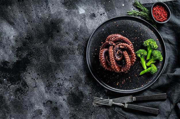 Gekookte octopus met broccoli op een plaat. zwart oppervlak. bovenaanzicht. kopieer ruimte Premium Foto