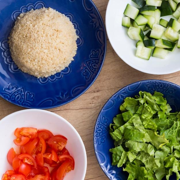 Gekookte rijst met verschillende gesneden groenten in kommen Gratis Foto