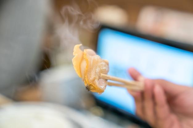Gekookte shell in eetstokjes met rook in japans restaurant Premium Foto