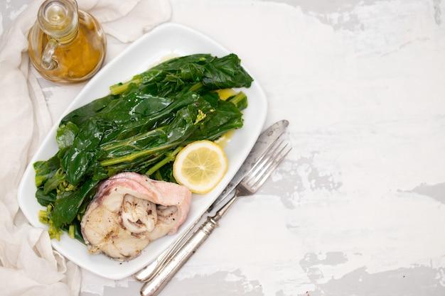 Gekookte vis met citroen en groenten op witte schotel Premium Foto