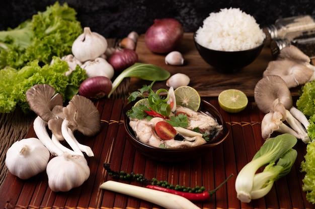 Gekookte visinfusie met tomaten, champignons, koriander, bosui en citroengras in een kom Gratis Foto