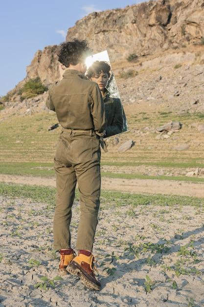 Gekruld stijlvol model met een bruine jumpsuit in de spiegel kijkend met een verwarde uitdrukking Gratis Foto