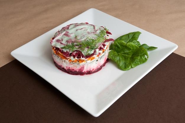 Gelaagde shuba-salade met biet, aardappel, wortel, zure haring en mayonaise. Premium Foto