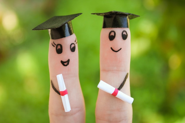 Gelaat op de vingers geschilderd. studenten met hun diploma Premium Foto