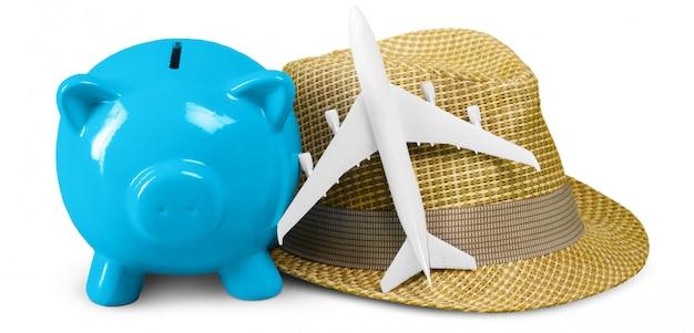 Geld besparen, blue pig-spaarpot, hoed en minivliegtuig Premium Foto