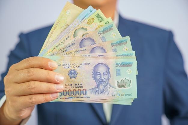 Geld in vietnam bij de hand houden zakenman draagt een blauwe pak Premium Foto