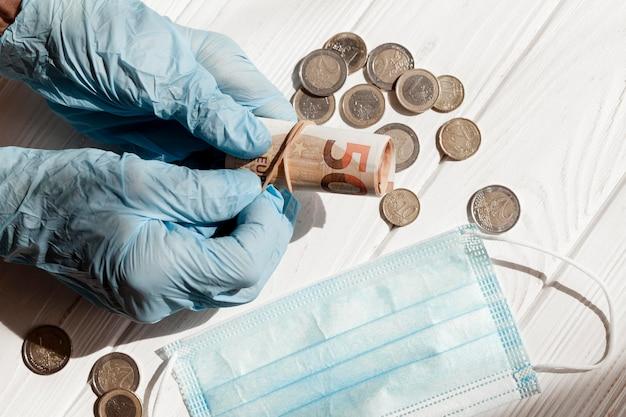 Geld met beschermende handschoenen en medische masker Gratis Foto