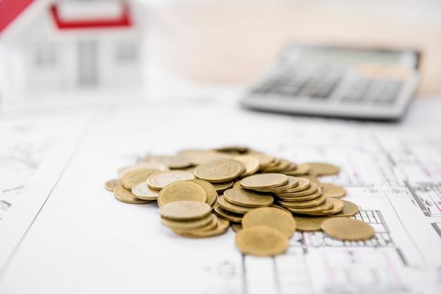 Geld op blauwdrukdocument met vaag huismodel en calculator op achtergrond Premium Foto