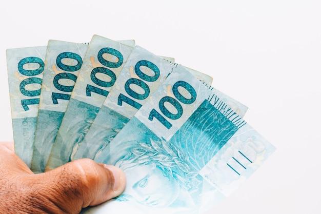 Geld uit brazilië. echte bankbiljetten, braziliaans geld in de hand van een zwarte man. aantekeningen van 100 reais. concept van inflatie, economie en bedrijfsleven. lichte achtergrond Premium Foto