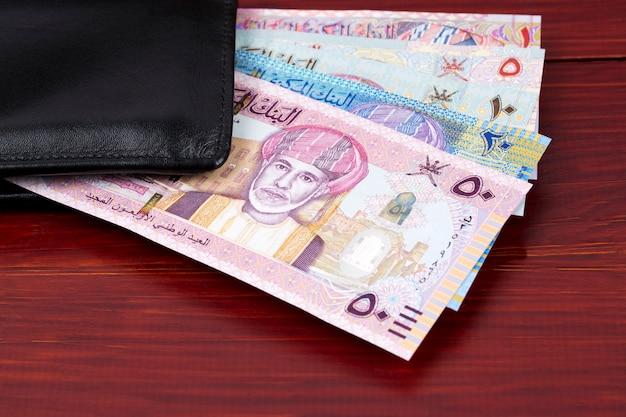 Geld van oman - rial in de zwarte portemonnee Premium Foto