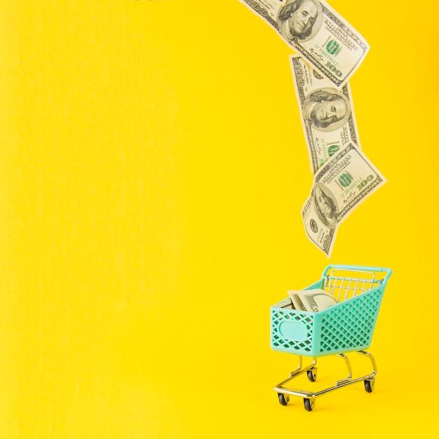 Geld vliegt vanuit supermarkt winkelwagen Gratis Foto