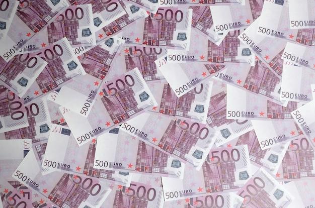 Geldachtergrond die uit paarse vijf honderd euro rekeningen bestaat die over het scherm worden uitgespreid Premium Foto
