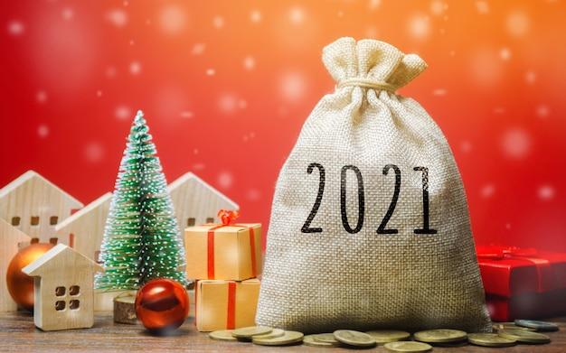 Geldzak 2021, kerstboom, miniatuurhuisjes en cadeautjes. Premium Foto